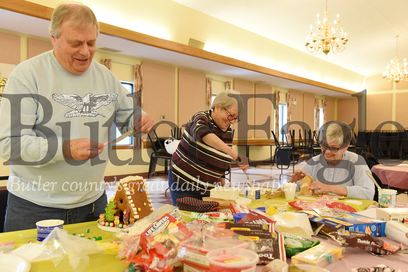Harold Aughton/Butler Eagle: (left - right) Bob Demask, Patricia Woods and Kitty Aul make gingerbread houses at the Evans City Senior Center, Tues., Dec. 3, 2019.