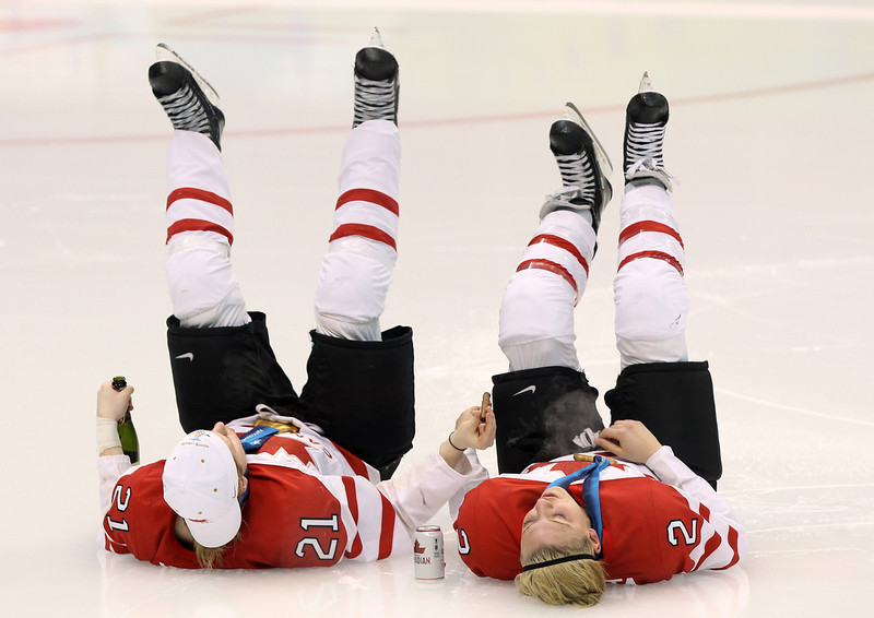 . Canada\'s Haley Irwin, left, and Meghan Agosta kick their feet into the air as they share a cigar at centre ice following their gold medal win over the United States at the 2010 Winter Olympic Games in Vancouver.  (AP Photo/Jonathan Hayward, CP, File)