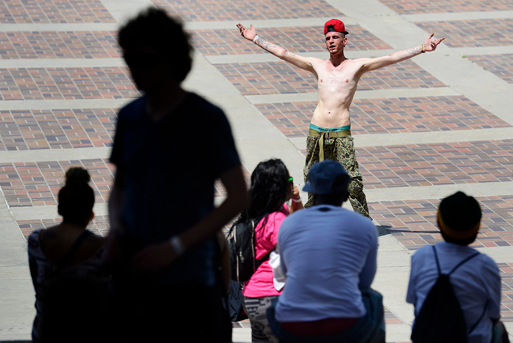 . Angel Coronado entertains festival goers sitting on the Civic Center steps during the Denver 420 Rally held Saturday. (Photo by Kira Horvath/ The Denver Post)