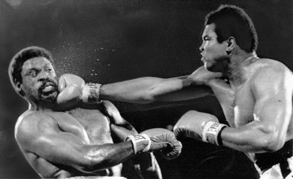 Description of . Muhammad Ali hits Ron Lyle with a hard right to the chin during action in their title fight in Las Vegas. Ali won the fight with a TKO in the 11th round. (AP Wirephoto/ May 16, 1975)