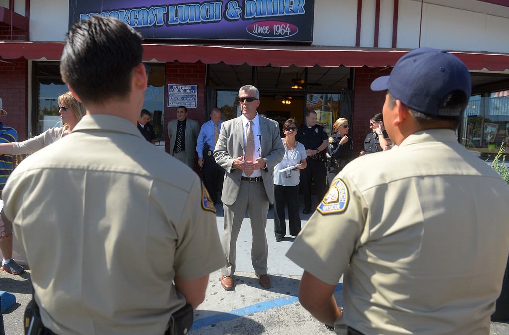 """. Search and rescue volunteers are briefed before heading out to pass out fliers in a neighborhood surrounding 7th Street and Orange Avenue in Long Beach, CA on Tuesday, May 13, 2014. The LBPD is looking for witnesses or anyone with knowledge of the March 24 shooting at the Cerritos Mini Market which left owner Felix Avela in critical condition after being shot during a robbery. The suspect is described as a black male in his late teens or early 20\'s with an average build and wearing a black hoodie sweatshirt with the word \""""Cali\"""" on the front. Anyone with info is asked to call LBPD at 562-570-7464 or 800-222-TIPS. (Photo by Scott Varley, Daily Breeze)"""