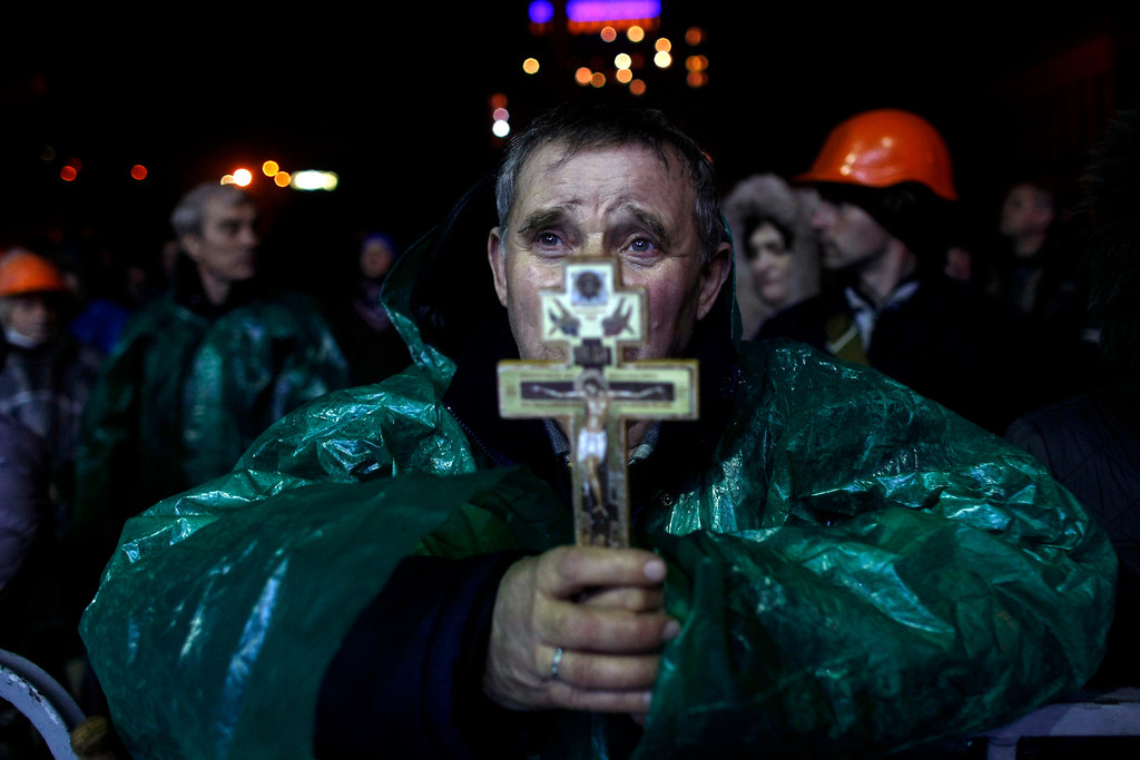 . An anti-government protester holds a crucifix as he prays at Independence Square in Kiev, Ukraine, Thursday, Feb. 20, 2014.  (AP Photo/ Marko Drobnjakovic)