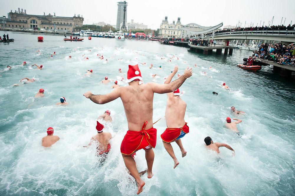. Competitors jump into the sea during the 103rd Barcelona Traditional Christmas Swimming Cup at the Old Harbour of Barcelona on December 25, 2012 in Barcelona, Spain. The Copa Nadal is organized by the Barcelona Swimming Club and involves competitors swimming across some 200 meters of water in the harbor. Launched in 1908 the event has only been suspended three times when the Spanish Civil War interrupted proceedings between 1936 and 1938.  (Photo by David Ramos/Getty Images)