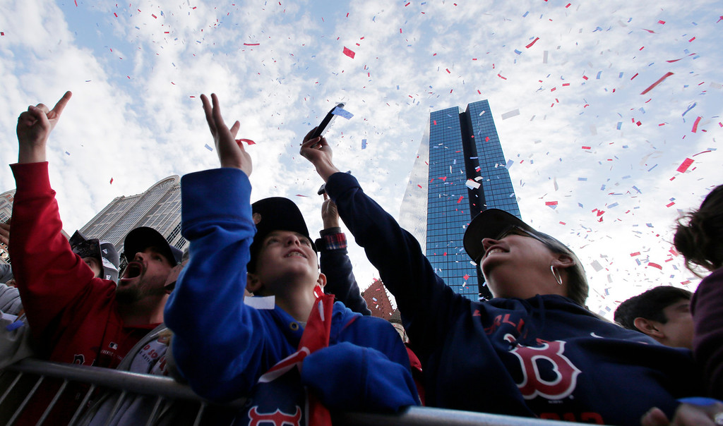 . Boston Red Sox fans reach up for flying confetti during a parade in celebration of the baseball team\'s World Series win, Saturday, Nov. 2, 2013, in Boston. (AP Photo/Charles Krupa)