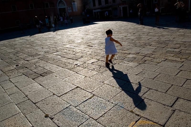 Little girl running on Santo Stefano square (Campo Santo Stefano), San Marco quarter, Venice, Italy. Model release available.