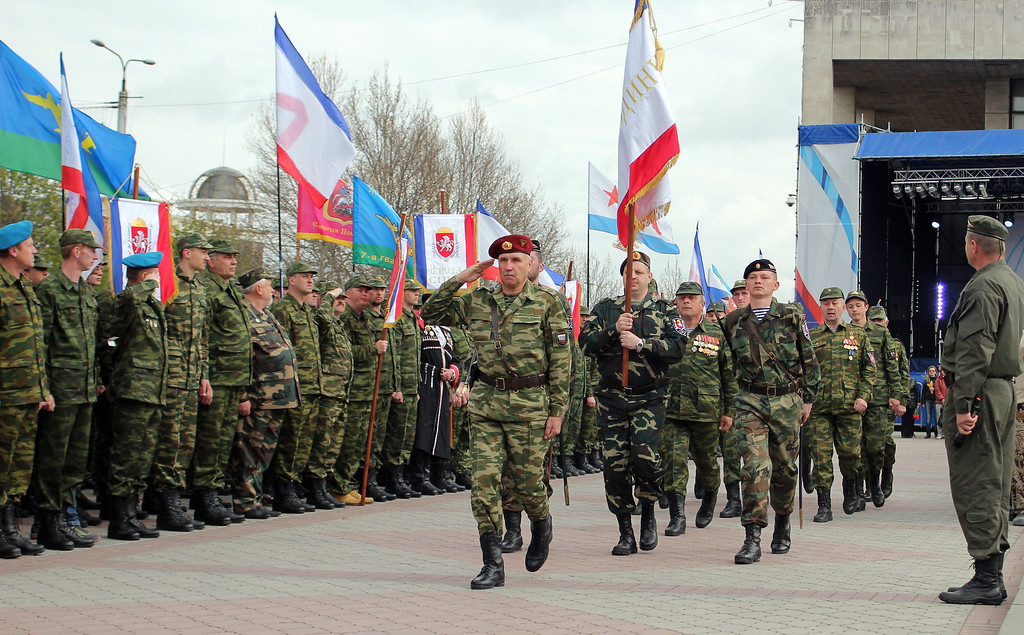 . Members of the pro-Russian self defense forces carry Crimea\'s flag during a parade to celebrate the 70th anniversary of the peninsula\'s capital Simferopol liberation from Nazi Germany troops during the World War II in Simferopol on April 13, 2014. Crimea\'s largely Russian-speaking residents voted in March to become part of Russia, in a hastily organised referendum held as Russian troops patrolled the region.  AFP PHOTO/ YURIY LASHOV