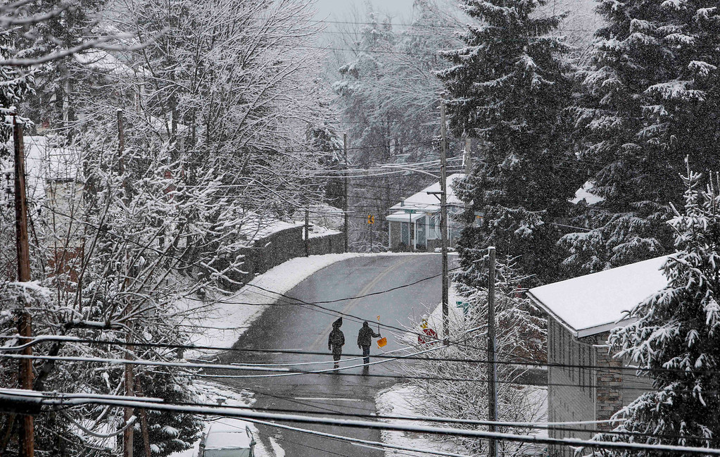 . Two men walk with snow shovels down Richwood Avenue in Morgantown, W.Va., on Wednesday, March 6, 2013.   (AP Photo/David Smith)