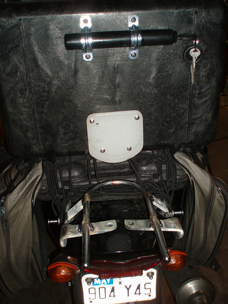 """PELICAN TOP CASE INSTALLATION: The lock is attached to the case with 1"""" conduit clamps. I cut a piece off an old plastic cutting board (sorry dear) and bolted it to the case using 1/2"""" spacers so as to slide under the front of the U-Bar. Later, I'll make an open luggage rack to attach to the U-Bar bracket. Of course, the whole thing comes off with 4 bolts and the OEM grab bar can go right back on like it never even happened."""