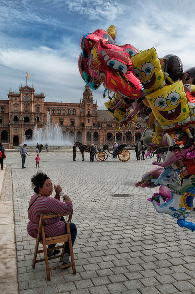 Gypsy woman selling balloons in the Plaza de Espana. The Plaza de España is a plaza located in the Parque de María Luisa, built in 1928 for the Ibero-American Exposition of 1929. It is a landmark example of the Renaissance Revival style in Spanish architecture.  Sevilla, Spain, 2011.