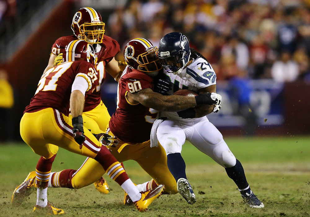 . Doug Worthington #90 of the Washington Redskins tackles  Marshawn Lynch #24 of the Seattle Seahawks in the second half during the NFC Wild Card Playoff Game at FedExField on January 6, 2013 in Landover, Maryland.  (Photo by Al Bello/Getty Images)