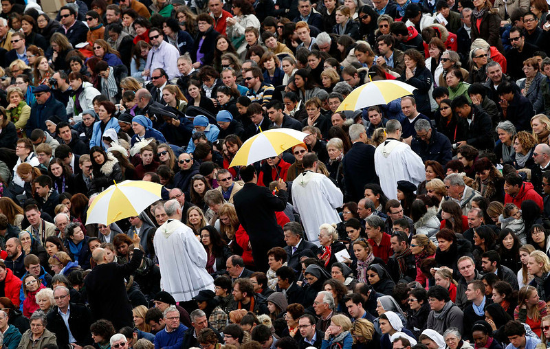 . Priests under umbrellas give communion to faithful as Pope Francis leads the Easter mass in St. Peter\'s Square at the Vatican March 31, 2013.   REUTERS/Alessandro Bianchi