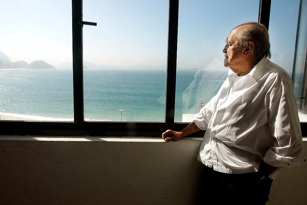 . Brazilian architect Oscar Niemeyer looks at the Copacabana beach from his office in Rio de Janeiro on this June 16, 2003.  Niemeyer, a towering patriarch of modern architecture who shaped the look of contemporary Brazil and whose inventive, curved designs left their mark on cities worldwide, died late on December 5, 2012. He was 104. Niemeyer had been battling kidney and stomach ailments in a Rio de Janeiro hospital since early November. His death was the result of a lung infection developed this week, the hospital said, little more than a week before he would have turned 105. REUTERS/Sergio Moraes