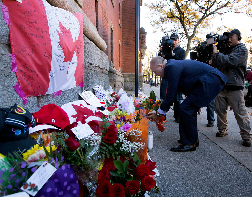 . Bruce Heyman, the American Ambassador to Canada, places flowers at a makeshift memorial to Cpl. Nathan Cirillo outside of The Lieutenant-Colonel John Weir Foote Armoury in Hamilton, Ontario on Thursday, Oct. 23, 2014.   (AP Photo/The Canadian Press, Peter Power)