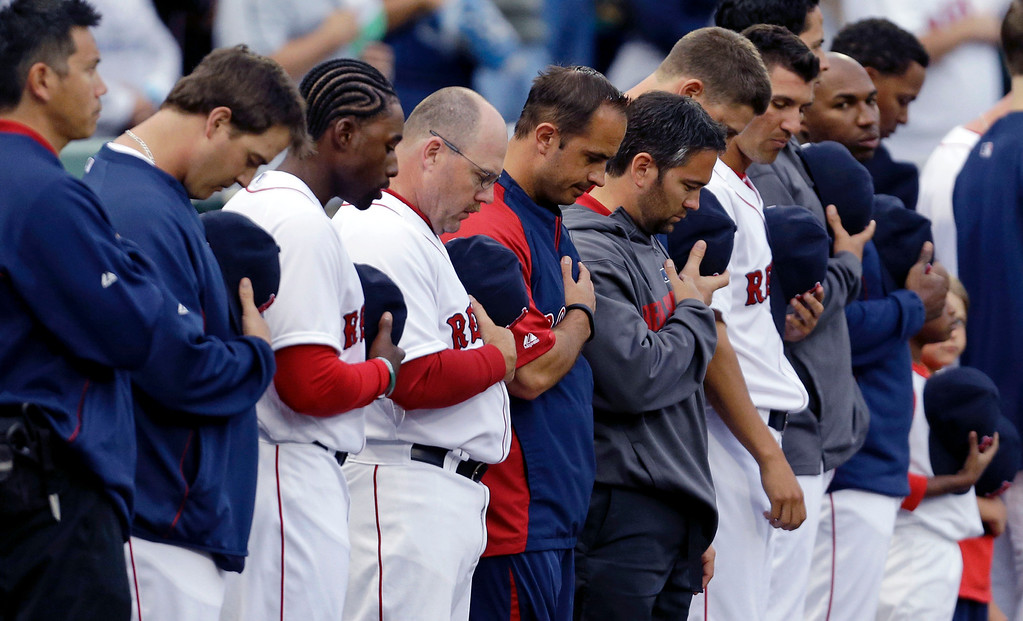 . Members of the Boston Red Sox bow their heads during a moment of silence for two Boston firefighters who died fighting a fire Wednesday, before the start of an exhibition baseball game against the Minnesota Twins. (AP Photo/Gerald Herbert)
