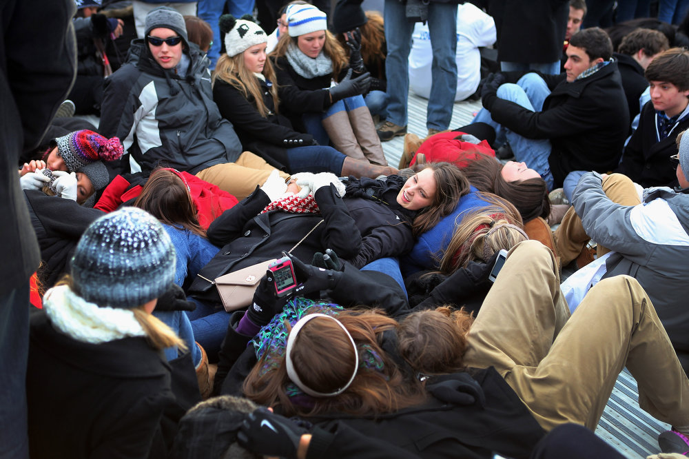 . People lie on the ground as they gather near the U.S. Capitol building on the National Mall for the Inauguration ceremony on January 21, 2013 in Washington, DC.  U.S. President Barack Obama will be ceremonially sworn in for his second term today.  (Photo by Joe Raedle/Getty Images)