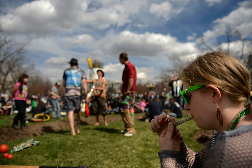 . Kylee Thorson of Denver lighting up at the annual 420 Rally at Civic Center Park in downtown Denver April 20, 2013 Denver, Colorado. (Photo By Joe Amon/The Denver Post)