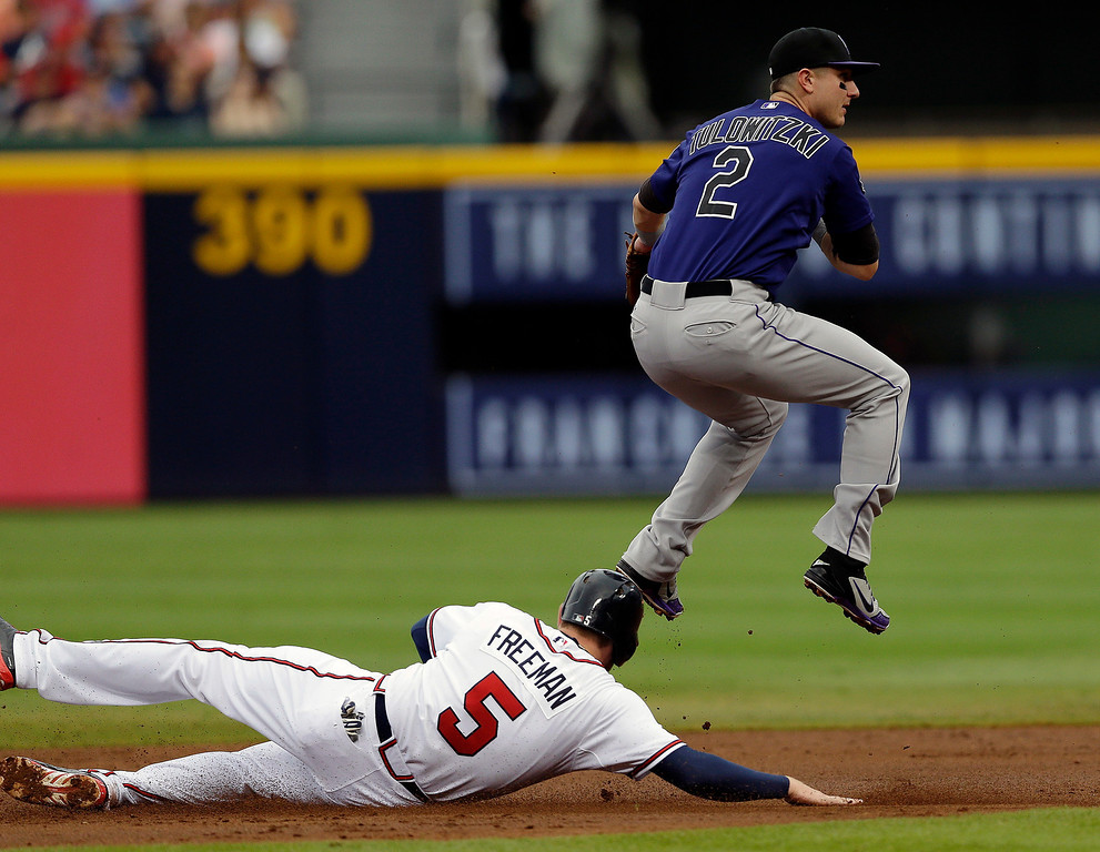 . Colorado Rockies shortstop Troy Tulowitzki (2) avoids Atlanta Braves\' Freddie Freeman (5) while turning a double play on a Brian McCann ground ball in the first inning of a baseball game in Atlanta, Wednesday, July 31, 2013. (AP Photo/John Bazemore)