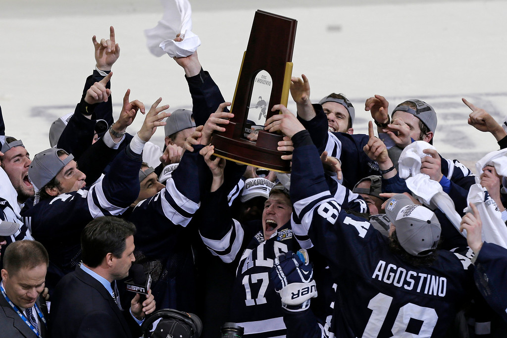 . Yale captain Andrew Miller (17) hoists the trophy for winning the NCAA men\'s college hockey Frozen Four national championship game over Quinnipiac 4-0, in Pittsburgh, Saturday, April 13, 2013.  (AP Photo/Gene Puskar)