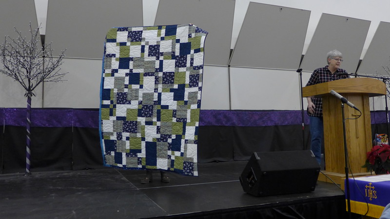 Lynda Patriarche showing a quilt made by the Scrap Fever Group as a charity quilt.  Members made the blocks, Pam Marcus pieced the top and John Putnam quilted it.  Pattern is High Five #1.