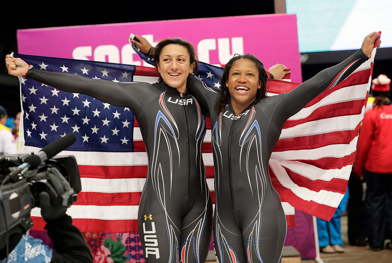 . Silver medal winners Elana Meyers and Lauryn Williams, right, hold up the flag after their final run during the women\'s bobsled competition at the 2014 Winter Olympics, Wednesday, Feb. 19, 2014, in Krasnaya Polyana, Russia. (AP Photo/Jae C. Hong)
