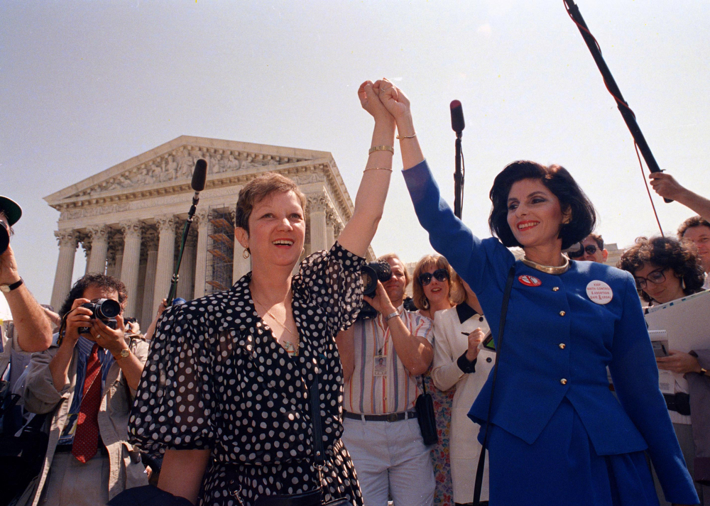 . Norma McCorvey, Jane Roe in the 1973 court case, left, and her attorney Gloria Allred hold hands as they leave the Supreme Court building in Washington, DC., Wednesday, April 26, 1989 after sitting in while the court listened to arguments in a Missouri abortion case. The court\'s decision may overturn the 1973 Roe v Wade case which legalized abortion. (AP Photo/J. Scott Applewhite)