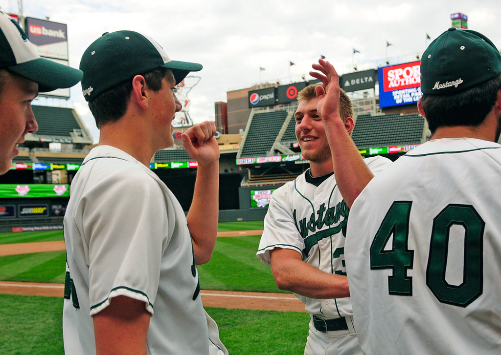 . Mounds View starter Max Knutson, second from right, who pitched all seven innings for the Mustangs, high-fives his teammates after their 8-0 win over Rocori.  (Pioneer Press: Scott Takushi)