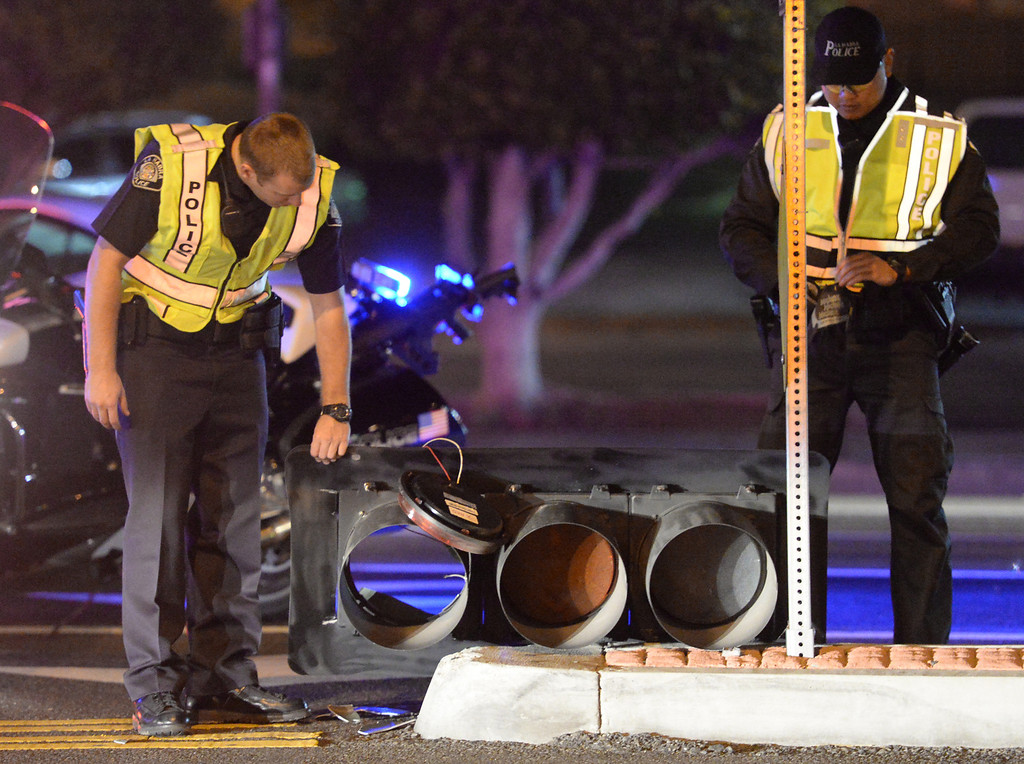 . La Habra Police officers prepare to carry off a traffic signal that fell on traffic lanes at the intersection of Beach Boulevard and Lambert Road after the 5.1 earthquake in La Habra on Friday March 28, 2014. (Staff Photo by Keith Durflinger/Whittier Daily News)