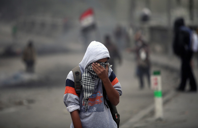 . An Egyptian protester reacts from tear gas during clashes with riot police, not seen, near Tahrir Square, Cairo, Egypt, Monday, Jan. 28, 2013.Health and security officials say a protester has been killed in clashes between rock-throwing demonstrators and police near Tahrir Square in central Cairo. The officials say the protester died Monday on the way to the hospital after being shot.  (AP Photo/Khalil Hamra)