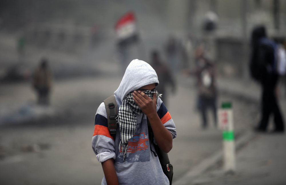 Description of . An Egyptian protester reacts from tear gas during clashes with riot police, not seen, near Tahrir Square, Cairo, Egypt, Monday, Jan. 28, 2013.Health and security officials say a protester has been killed in clashes between rock-throwing demonstrators and police near Tahrir Square in central Cairo. The officials say the protester died Monday on the way to the hospital after being shot.  (AP Photo/Khalil Hamra)