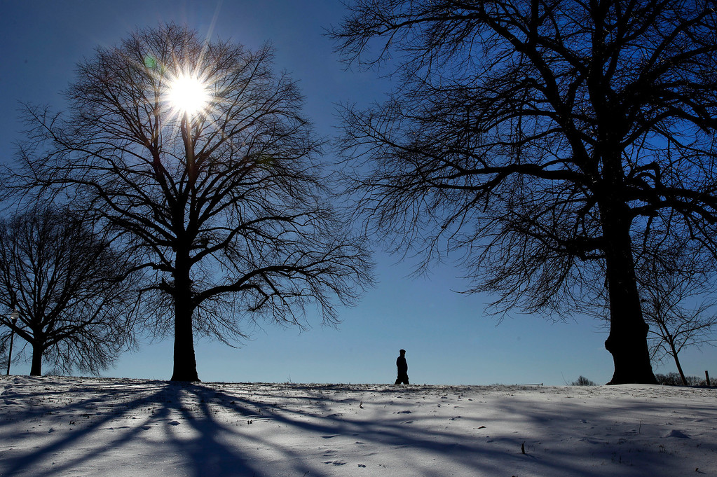 . A man walks in Baltimore\'s Patterson Park, Wednesday, Jan. 22, 2014, where temperatures remain firmly below freezing. The Northeast started to clean up from a winter storm that swirled up the coast Tuesday. (AP Photo/Patrick Semansky)