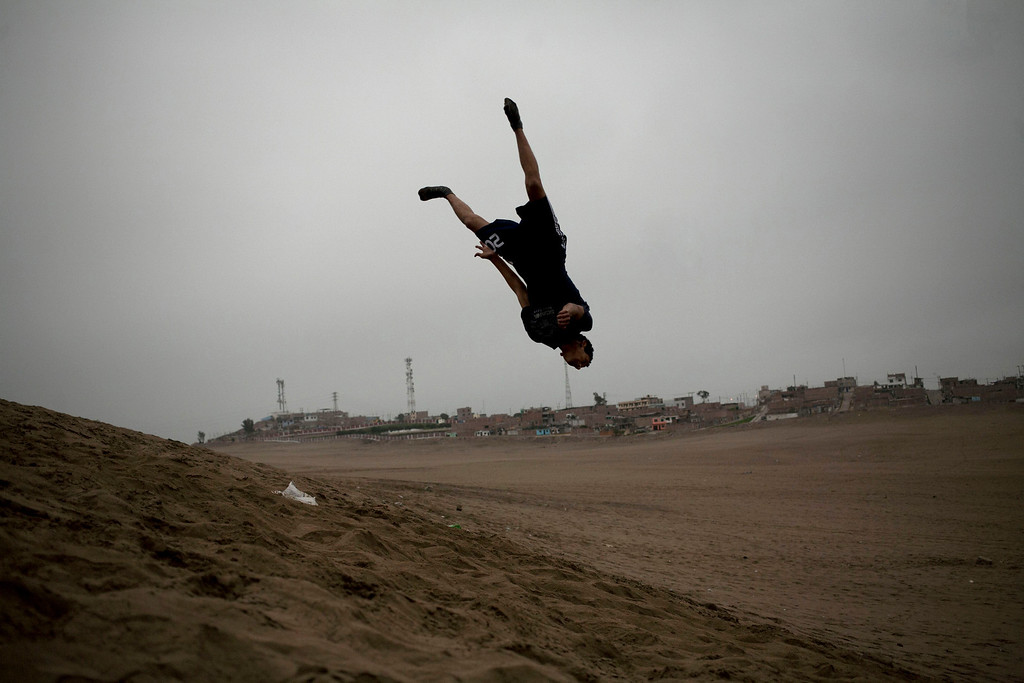 ". In this July 11, 2013 photo, Cristian Lozada, 18, practices stunts on the sands of the Pachacamac ruins in Lima, Peru. For roughly four months a year, the sun abandons Peru\'s seaside desert capital, suffocating it under a ponderous gray cloudbank and fog that coats the city with nighttime drizzles. The cold Humboldt current that runs north from Antarctica along the coast is the culprit, colliding with the warmer tropical atmosphere to create the blinding mists called ""garua\"" in coastal Chile and Peru. (AP Photo/Rodrigo Abd)"