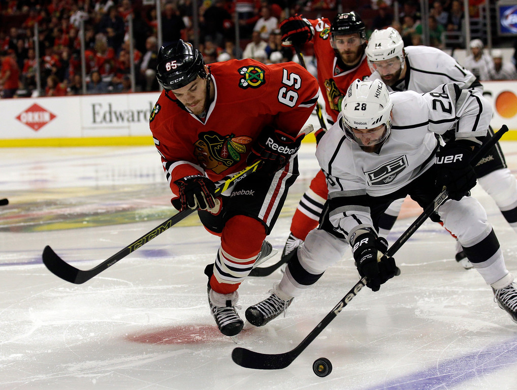 . Los Angeles Kings center Jarret Stoll (28) battles for the puck with Chicago Blackhawks center Andrew Shaw (65) during the second period in Game 7 of the Western Conference finals in the NHL hockey Stanley Cup playoffs Sunday, June 1, 2014, in Chicago. (AP Photo/Nam Y. Huh)