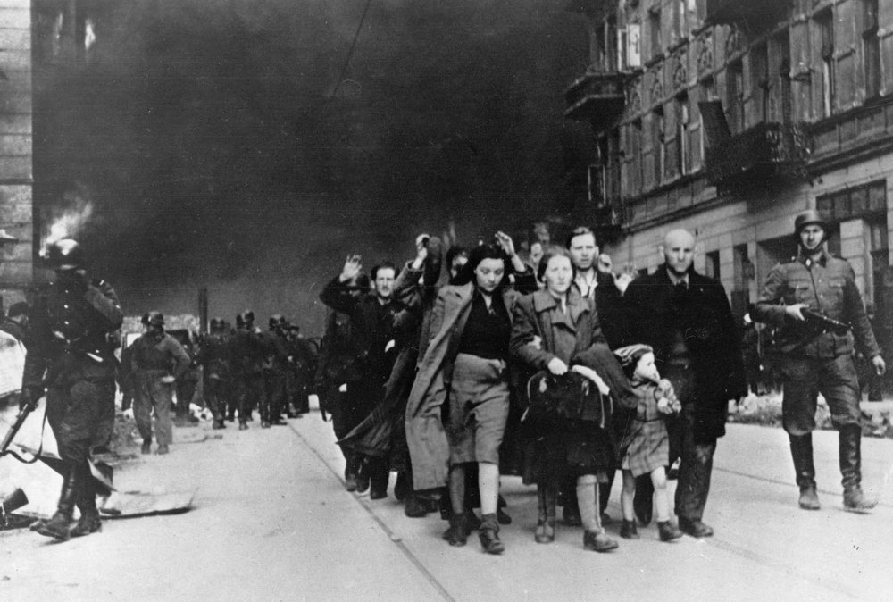 """. In this in April/May 1943 photo, a group of Polish Jews are led away for deportation by German SS soldiers during the destruction of the Warsaw Ghetto by German troops after an uprising in the Jewish quarter. The Nazis won out by systematically burning the ghetto to the ground, house by house. \""""Once the Germans began adopting that strategy there wasn\'t much that people armed with pistols, or even rifles and machine guns, could do,\"""" said historian Steve Paulsson, an expert on the period whose Jewish family survived the city\'s destruction. (AP Photo)"""