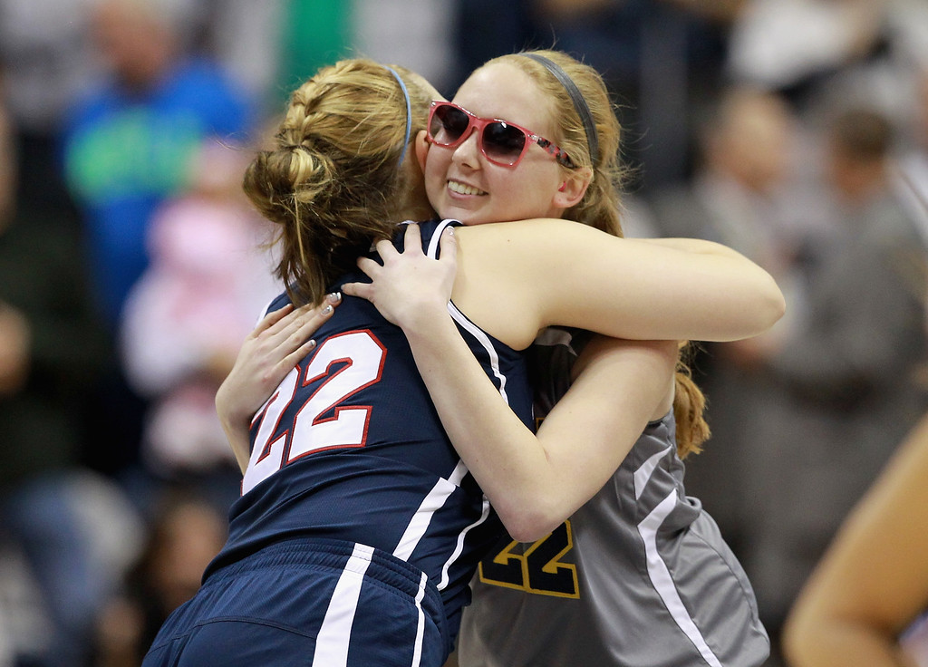 . Lauren Hill of Mount St. Joseph gets a hug from an opponent before the game against Hiram at Cintas Center on November 2, 2014 in Cincinnati, Ohio. Hill, a freshman, has terminal cancer and this game was granted a special waiver by the NCAA to start the season early so she could play in a game.  (Photo by Andy Lyons/Getty Images)