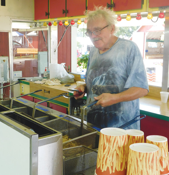 Donald Kish serves hot treats to Sunday's visitors at Ottenbacher Concessions during the 174th annual Medina County Fair. JONATHAN DELOZIER / GAZETTE
