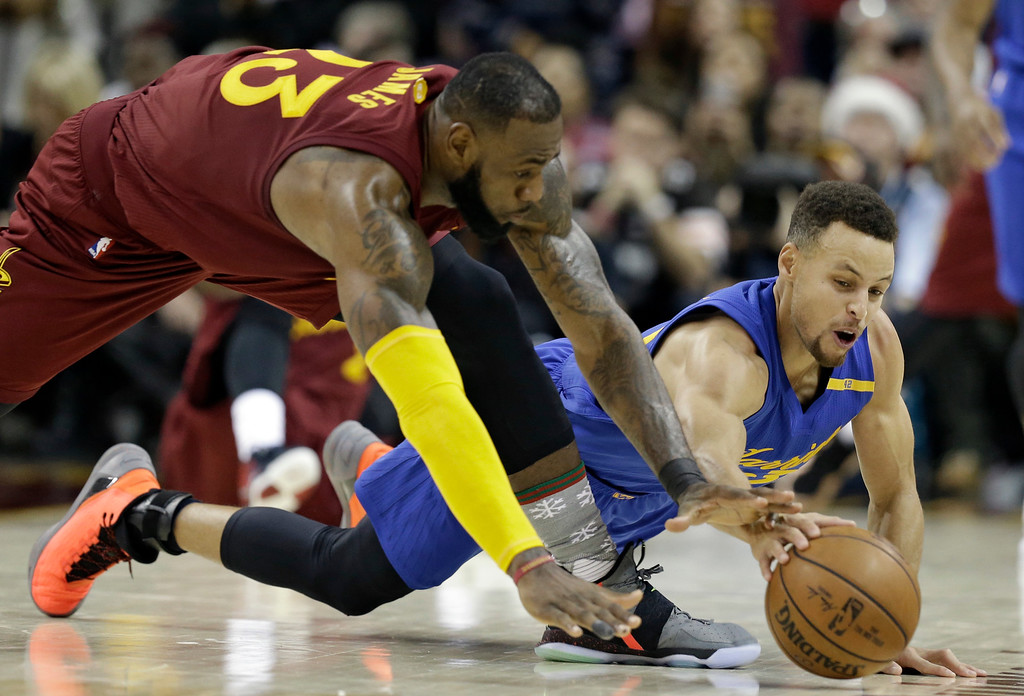 . Cleveland Cavaliers\' LeBron James, left, and Golden State Warriors\' Stephen Curry battle for a loose ball in the second half of an NBA basketball game, Sunday, Dec. 25, 2016, in Cleveland. The Cavaliers won 109-108. (AP Photo/Tony Dejak)