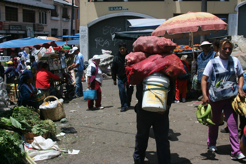 Heavy load of potatoes at the market in Quito