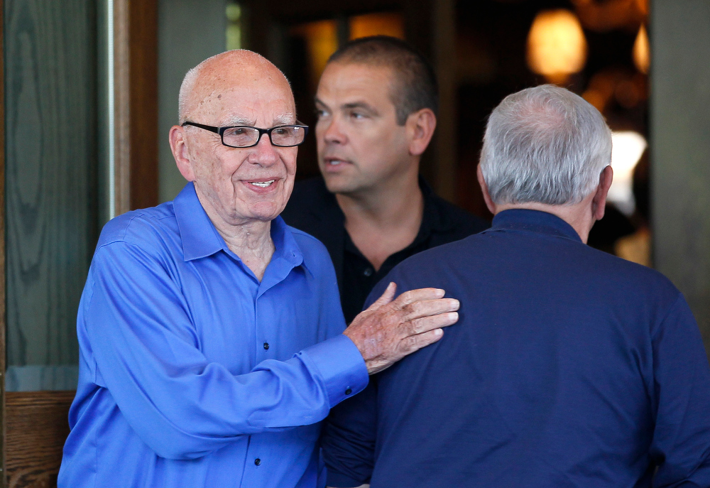 . Rupert Murdoch (L), chief executive of News Corp. and 21st Century Fox, pats NBA Commissioner David Stern (R) on the back upon his arrival for the annual Allen and Co. Conference at Sun Valley, Idaho July 9, 2013. At center is Lachlan Murdoch, board member of News Corp. and son of Rupert Murdoch. British lawmakers said on Tuesday they would recall Rupert Murdoch to clarify evidence he gave to them last year after he was secretly recorded belittling a police inquiry into alleged crimes committed by journalists on his papers. REUTERS/Rick Wilking