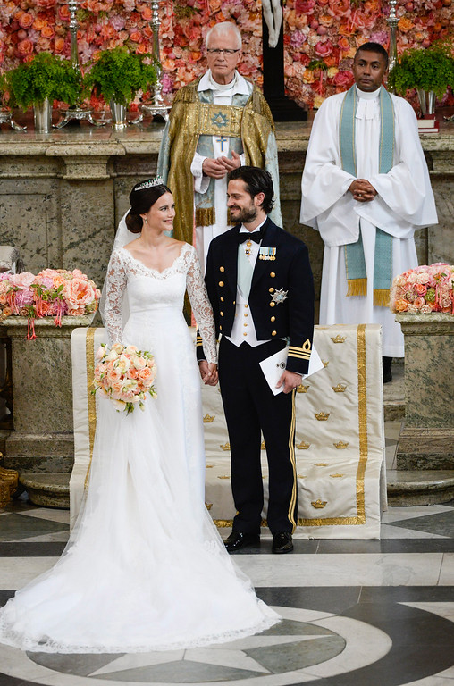. Sweden\'s  Prince Carl Philip stand with his bride, Sofia Hellqvist during their  wedding ceremony,  in Stockholm, Sweden,  Saturday, June 13, 2015.  The only son of King Carl XVI Gustaf and Queen Silvia has married his Swedish fiancee in a lavish ceremony in Stockholm. Prince Carl Philip and the former reality starlet and model Sofia Hellqvist, 30, tied the knot Saturday at the Royal Palace chapel before five European queens, a Japanese princess and dozens of other blue-blooded guests. The couple engaged in June 2014. In background are the Right Reverend Lars Goran Lonnermark, Royal Court Chief Chaplain  and the Reverend Michael Bjerkhagen. (Pontus Lundahl / TT via AP)