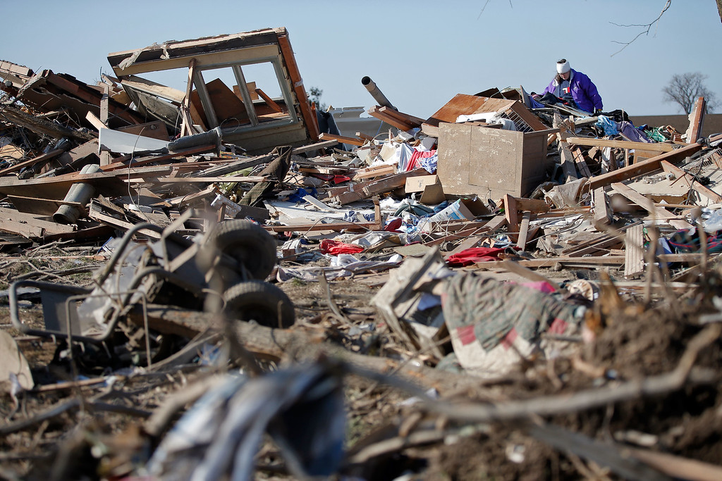 . Candy Trudell looks through the wreckage of her home on IL-64 after a tornado swept through the previous night, on April 10, 2015 in Rochelle, Illinois. According to reports, 11 people were injured and one person was killed when tornadoes and thunderstorms passed through the northwestern suburbs of Chicago. (Photo by Jon Durr/Getty Images)