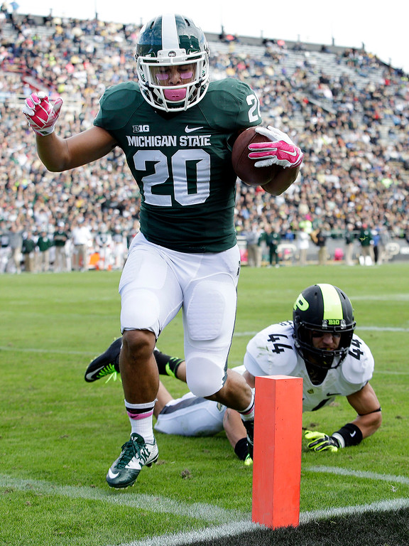 . Michigan State running back Nick Hill (20) scores a touchdown in front of Purdue safety Landon Feichter (44) during the first quarter of an NCAA college football game in West Lafayette, Ind., Saturday, Oct. 11, 2014. (AP Photo/AJ Mast)