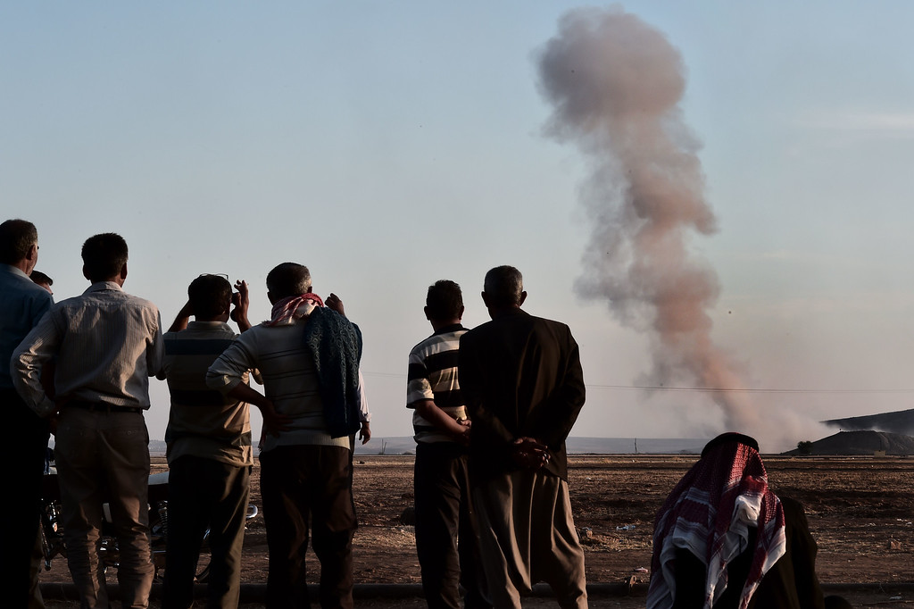 . People watch smoke rising from the Syrian town of Ain al-Arab, known as Kobane by the Kurds, after an air strike, on October 8, 2014 in the Turkish-Syrian border, in the southeastern village of Mursitpinar, Sanliurfa province. AFP PHOTO / ARIS MESSINISARIS MESSINIS/AFP/Getty Images