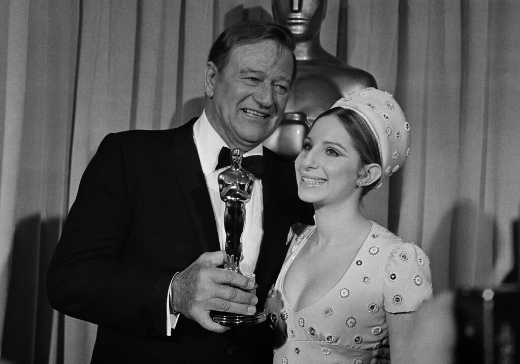 ". John Wayne is congratulated by Barbra Streisand as he accepts the Oscar for best actor for his performance in ""True Grit,\"" at annual Academy Awards at Los Angeles Music Center, April 7, 1970. (AP Photo)"