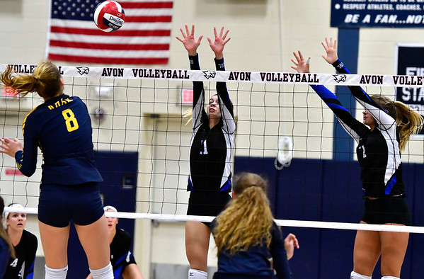 11/1/2018 Mike Orazzi | Staff Bristol Eastern's Ryley Plourde (11) and Zoe Lowe (7) with RHAM's Kaylin Hadley (8) during the CCC Volleyball Tournament at Avon High School Thursday night.