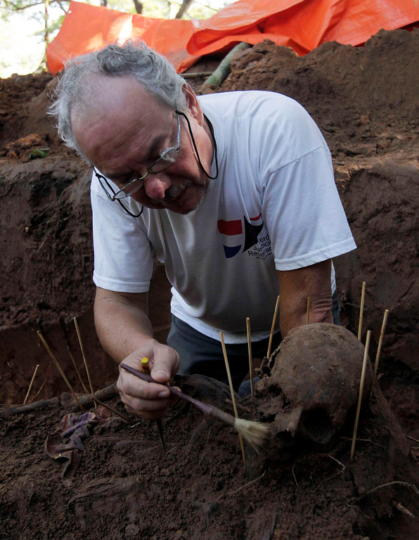 . Argentine forensic expert Rogelio Agustin Goiburu excavates human remains discovered in the grounds of a police barracks in Asuncion on March 21, 2013. According to the researchers, 15 more skeleton remains, likely to be victims of the 1954 to 1989 dictatorship under Alfredo Stroessner, were found in the last two days. Goiburu\'s father, Augustin Goiburu, was arrested in Argentina during the Dirty War and brought to Paraguay where he disappeared and was presumed killed. REUTERS/Jorge Adorno