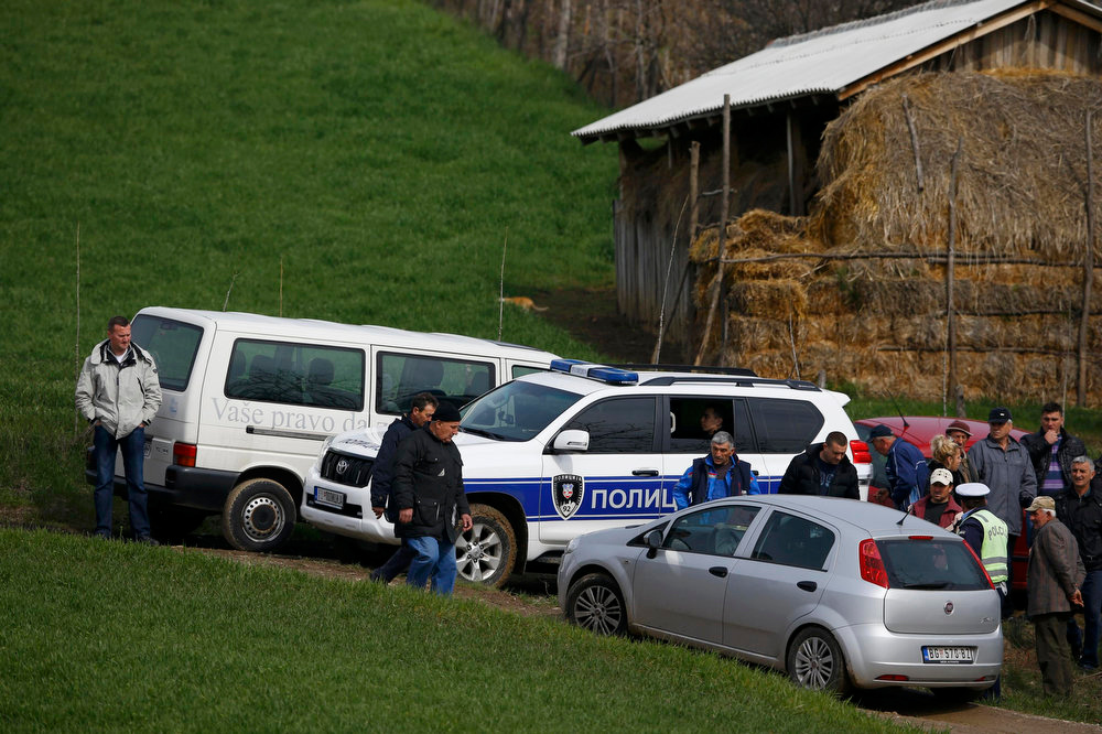 . Police and residents are pictured in the village of Velika Ivanca, about 40 km (25 miles) southwest of Belgrade April 9, 2013. A gunman shot dead 13 people, including his mother and son, in an early-morning rampage through a small Serbian village southwest of the capital Belgrade on Tuesday, authorities said. Those killed included a two-year-old child. The gunman, identified by police as Ljubisa Bogdanovic - a war veteran born in 1953 - also shot his wife before turning the gun on himself. Both were in critical condition in hospital, police said.     REUTERS/Marko Djurica