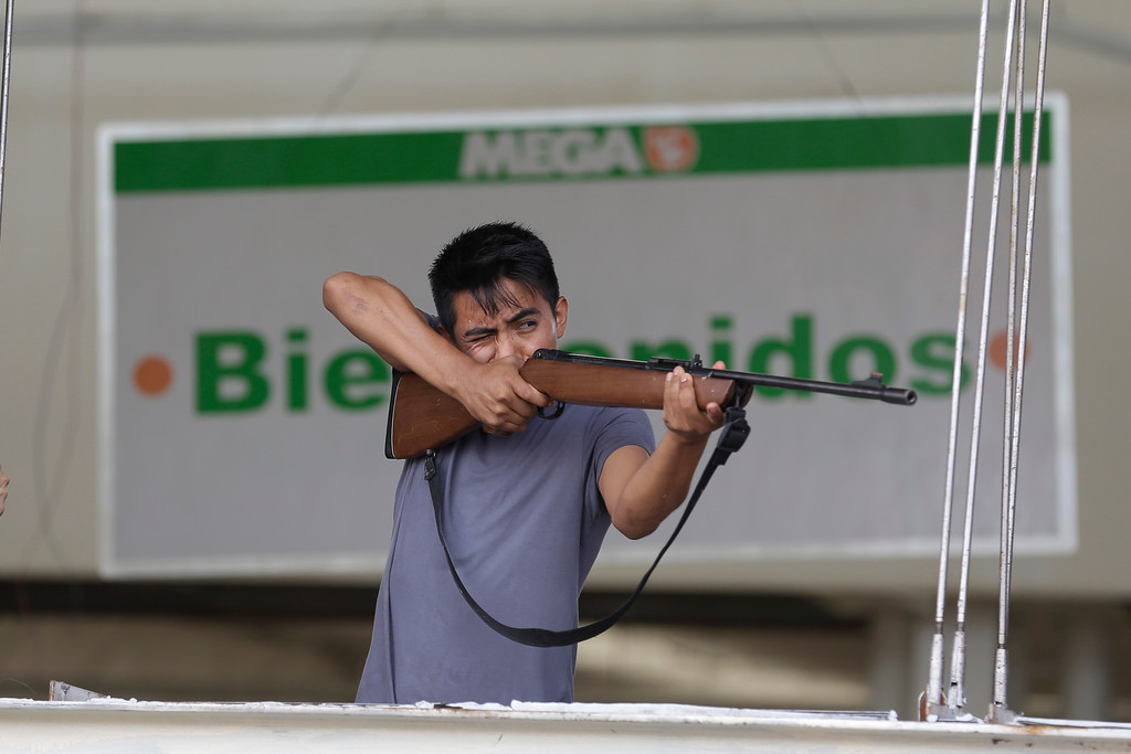 """. An employee from Mega Supermarket fires an air rifle at people trying to loot the store in Los Cabos, Mexico, Tuesday, Sept. 16, 2014. The sign in the background reads in Spanish \""""Welcome.\""""  According to employees the supermarket donated all the food in the store and established a system by which every person had 5 minutes to get whatever they could for free. Fights broke as other people inciting the crowd to loot. Desperate locals and tourists were in survival mode in the resort area of Los Cabos also on Wednesday, with electrical and water service still out three days after Hurricane Odile made landfall as a monster Category 3 storm. (AP Photo/Victor R. Caivano)"""