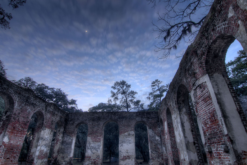 A sliver of the moon shines through a partly cloudy sky, creating a natural roof for the Old Sheldon Church Ruins in Yemassee, SC on Sunday, February 22, 2015. Copyright 2015 Jason Barnette  Sheldon Church, originally known as Prince William's Parish Church, was built in 1753. In 1779 British General Prevost marched from Savannah into South Carolina during the Revolutionary War and burned the church to the ground. It was rebuilt, but the church faced the fate again. In 1865 General Sherman marched from Savannah into South Carolina during the Civil War, known locally as the War Between the States, and burned the church to the ground again. It was never rebuilt.   Today the historic site is open to the public 24/7, and has become a popular destination for photographers and wedding ceremonies.
