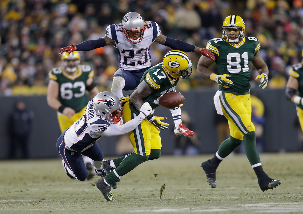 . GREEN BAY, WI - NOVEMBER 30:  Strong safety Tavon Wilson #27 of the New England Patriots grabs wide receiver Davante Adams #17 of the Green Bay Packers as strong safety Patrick Chung #23 jumps behind, in the first half of the NFL game at Lambeau Field on November 30, 2014 in Green Bay, Wisconsin. The Green Bay Packers defeats the New England Patriots 26-21. (Photo by Mike McGinnis/Getty Images) ***BESTPIX***