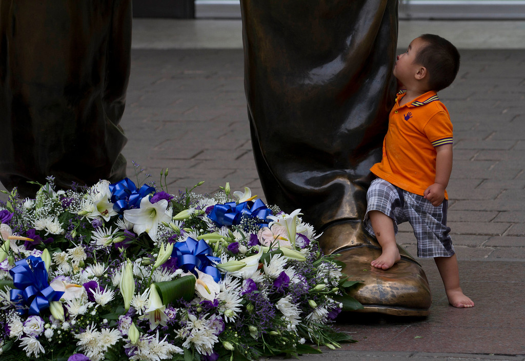. A child looks up at a giant bronze statue of former president Nelson Mandela, on Mandela Square in Sandton, Johannesburg, Friday, Dec 6.2013. Flower tributes were placed on the square after Mandela died Thursday at his Johannesburg home after a long illness. He was 95. (AP Photo/Athol Moralee)